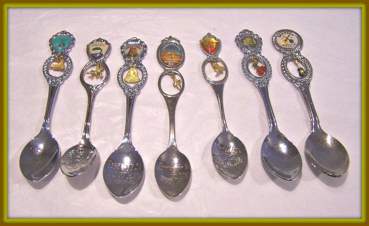 Here is an nice set of Vintage Collector Spoons with seven different Spoons with Souvenir Charms with Handle engraved. Door County, Branson Missouri, Cosmos Mystery Area, Corn Place, Devil's Tower Wyoming, World's Musky Capital,  &  the Arabia