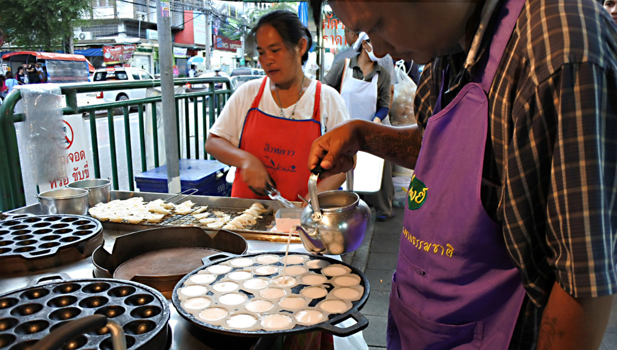 The preparation of the sweet coconut dessert 'khanom krok'. Here a vendor pours the coconut milk filling into cup-cake shaped moulds