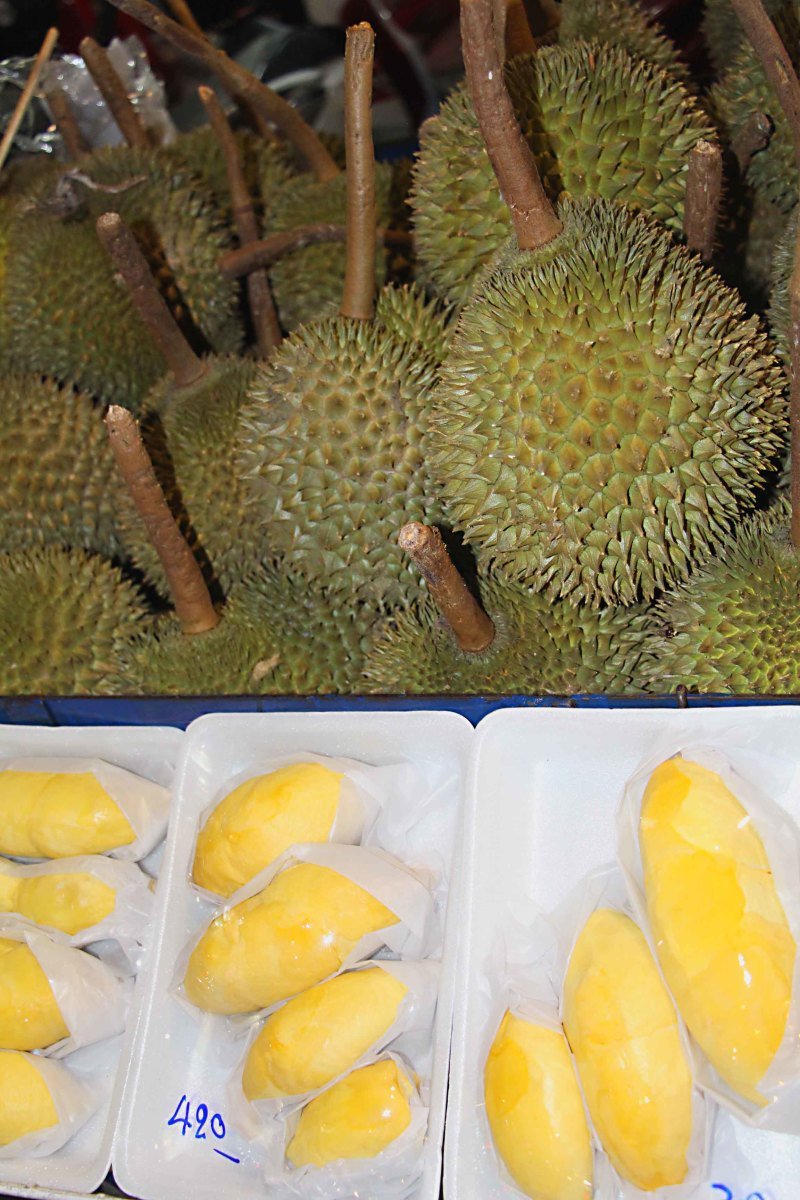 Durian - one of the most popular, yet pungently smelly, fruits! The whole fruit is shown above, and below it is sliced and cellophane wrapped ready for sale