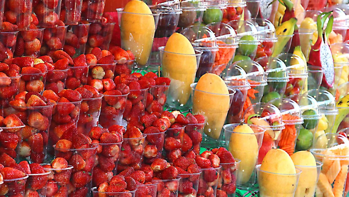 Fruits in the Chatuchak Street Market in Bangkok. Next to the strawberries are yellow peeled mangos and mixed fruits in plastic containers