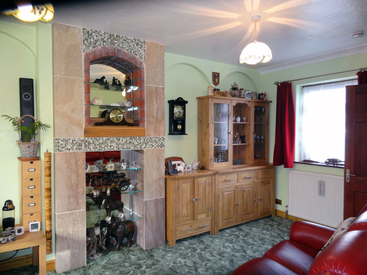 The old fireplace tiled and fitted with mirrored display shelves