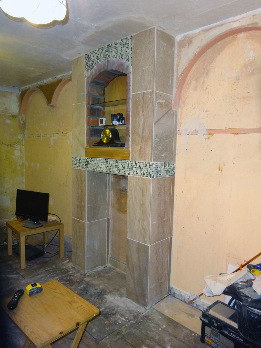 Living room cleared, walls stripped and fireplace tiled