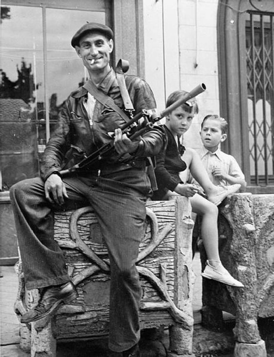 Watched by two small boys, a member of the FFI (French Forces of the Interior) poses with his Bren gun at Chateaudun, 1944