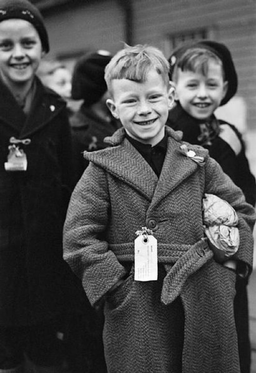 A small Dutch boy smiles for the camera upon arrival at Tilbury in Essex. He is carrying a small paper parcel under his arm, which contains all his luggage.