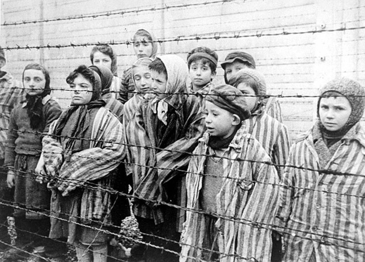 Child survivors of Auschwitz, wearing adult-size prisoner jackets, stand behind a barbed wire fence.