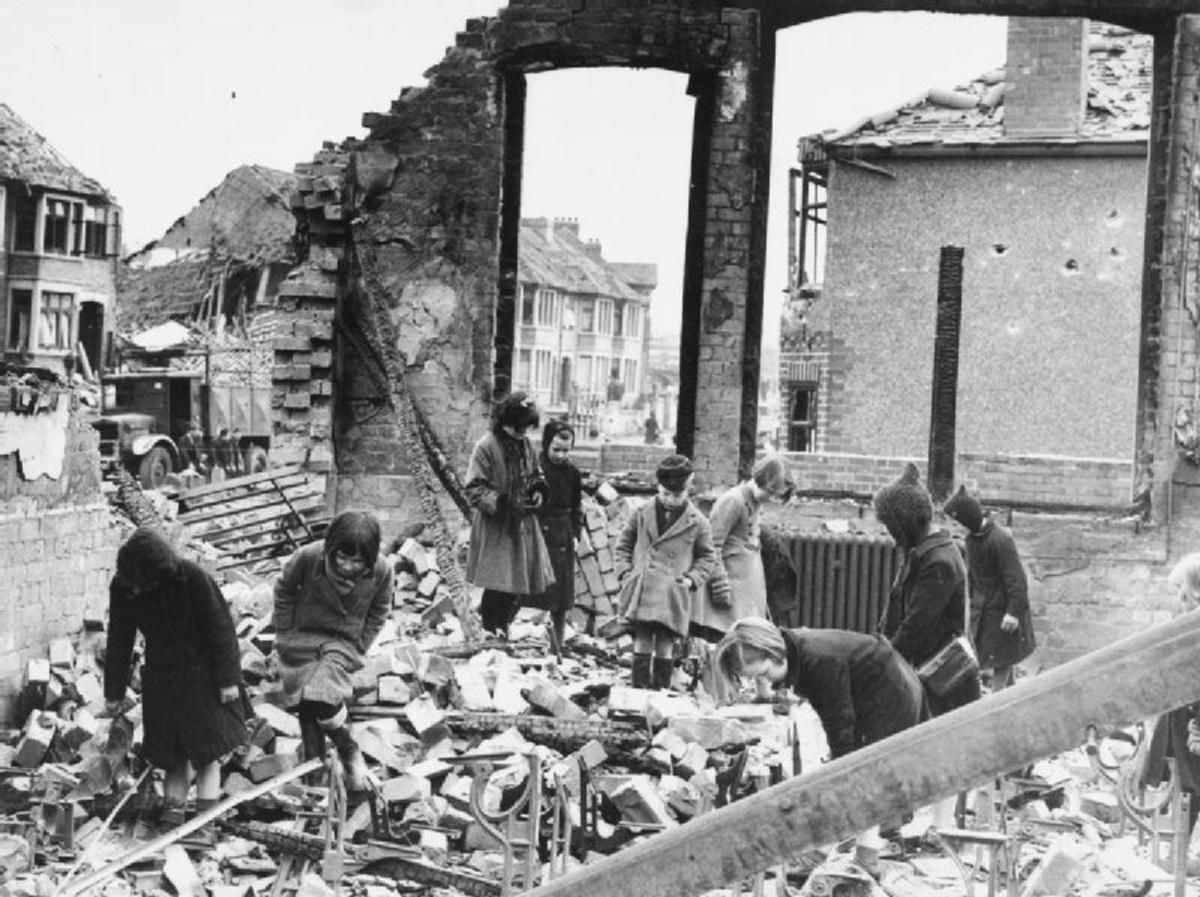 Children searching for books among the ruins of their school in Coventry after a night raid, 10 April 1941.