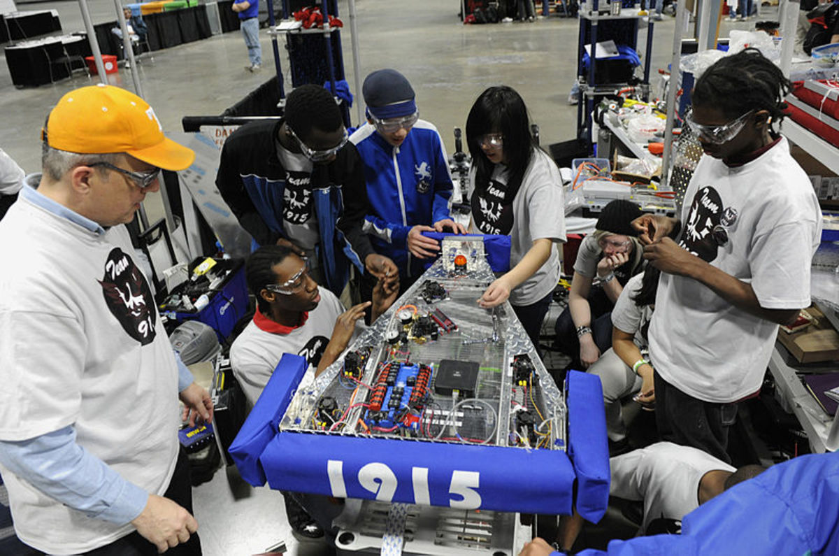 WASHINGTON (March 5, 2010) Cmdr. Jim Grove, from the Office of Naval Research Navy Reserve Program 38, left, helps students from McKinley Technology High School make adjustments to their robot during the For Inspiration and Recognition of Science and