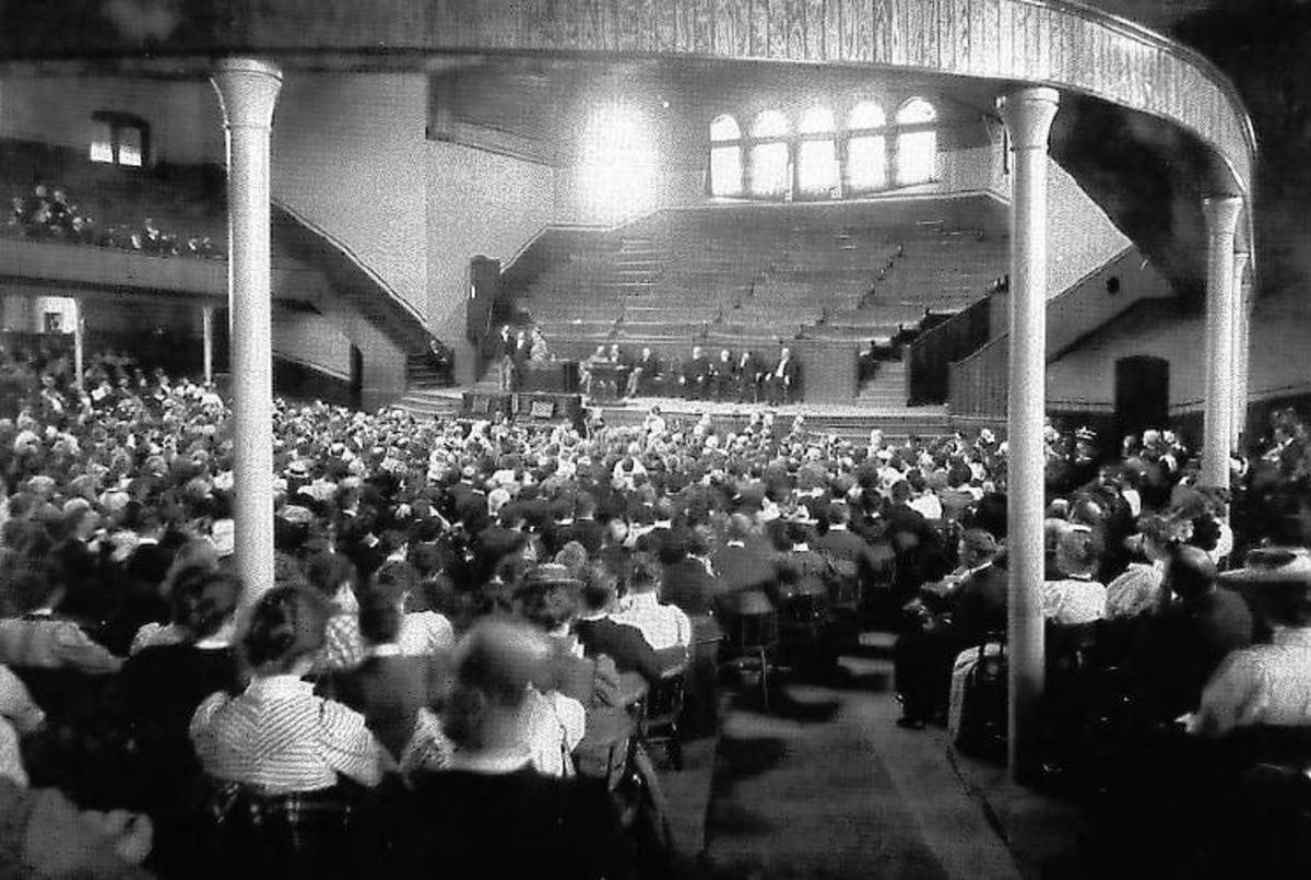 """Built in 1894, the auditorium on the Northfield campus seated 2,500 and was primarily constructed to serve the throngs of people attending Dwight L. Moody's summer conferences. In this photo, Moody is on stage, seated fourth from the right. Courtes"