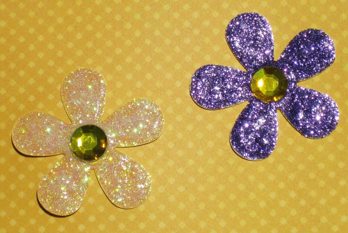 It is easy to create your own glitter glue flowers, Cut out a flower of your choice on heavy card stock. Paint the glitter glue on top of the flower petals, Allow to dry. Add a half gem to the top. Perfect for a scrapbook page or a card.
