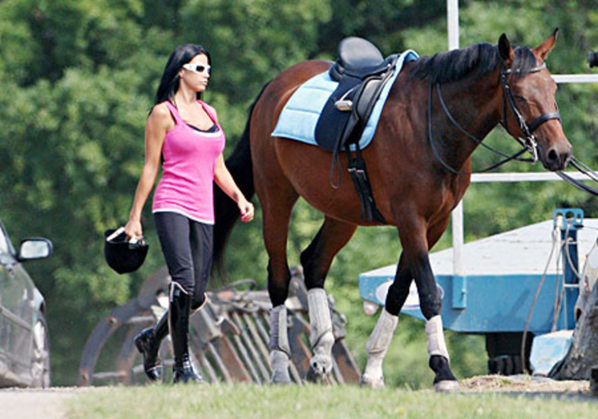 Katie Price walks her horse in Sussex, England, after a lesson
