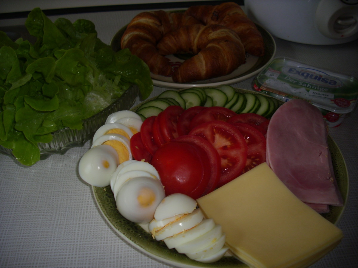 Croissants, eggs. tomatoes, cucumber, ham and cheese slices.
