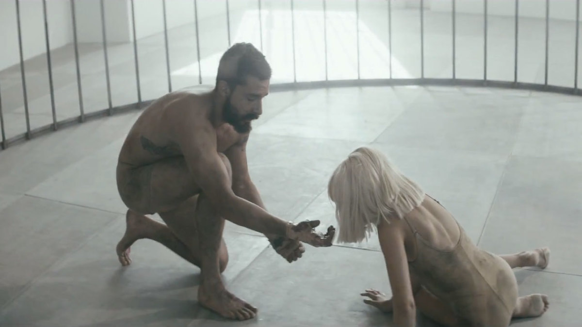 In one of the scenes in this music video, Shia holds out his hand to the beautiful Maddie as while portraying ths story inside of a cage.