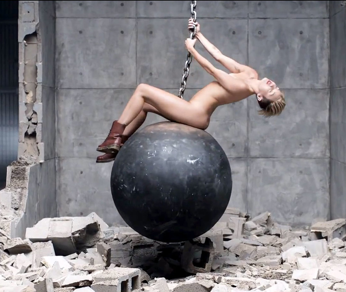 Miley Cyrus swings herself on the wrecking ball without anything to cover her nude body.