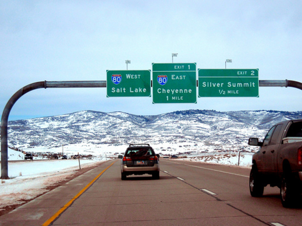 How are distances listed on freeway signs between cities determined?