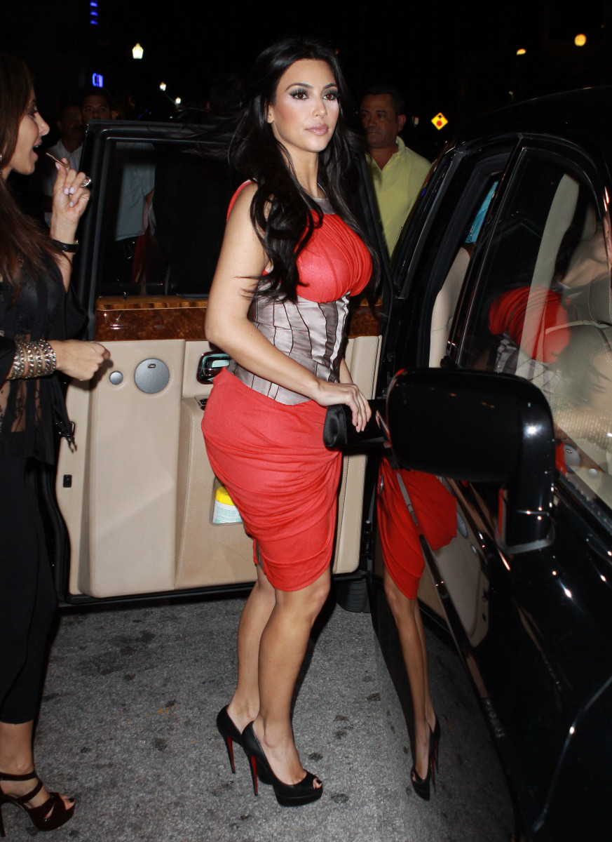 Kim Kardashian in a pretty red dress and high heels