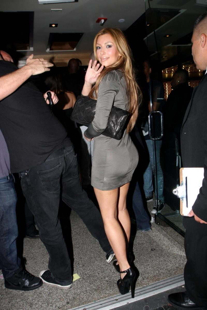Kim Kardashian wearing a bottom hugging dress and towering high heels