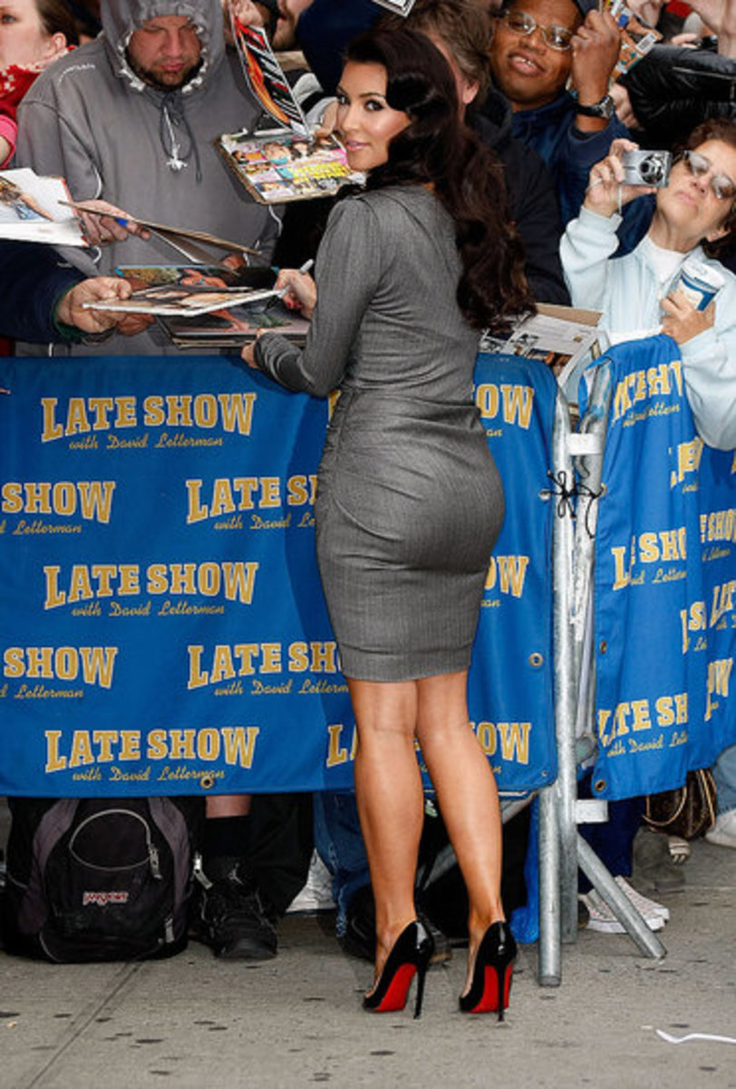 Kim Kardashian in a form fitting dress and towering high heels    Essence Atkins Legs