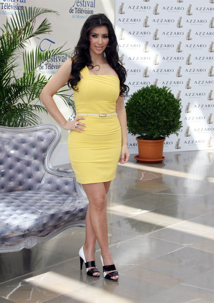 Kim Kardashian wearing a pretty yellow dress and high heels
