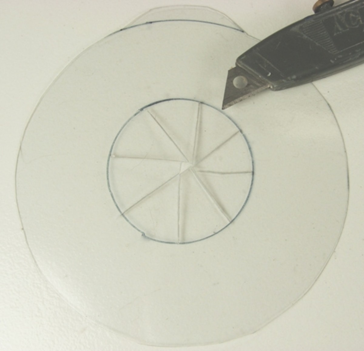 2. Using scissors or an razor blade knife cut out the large circle. To remove the center section first cut a spoke like pattern within the circle template then remove the small sections. Clean the plastic doughnut of all traces of the marking pen usi