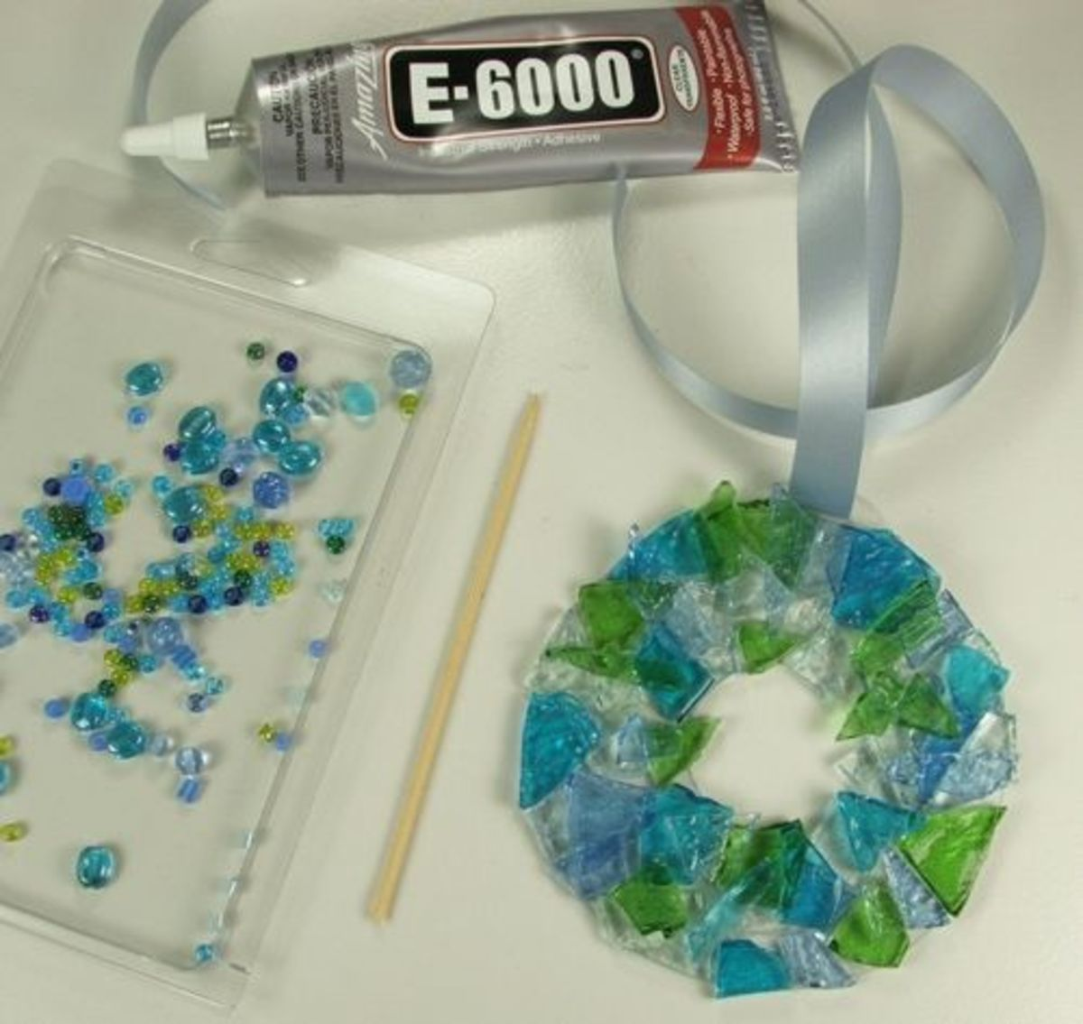 8. For the final touch add a few beads to your stunning piece. I first lay out all the beads that might work well with the colors of cobbles I have used. By placing the beads on a white paper plate or my favorite is to reuse a clam shell, you can eas