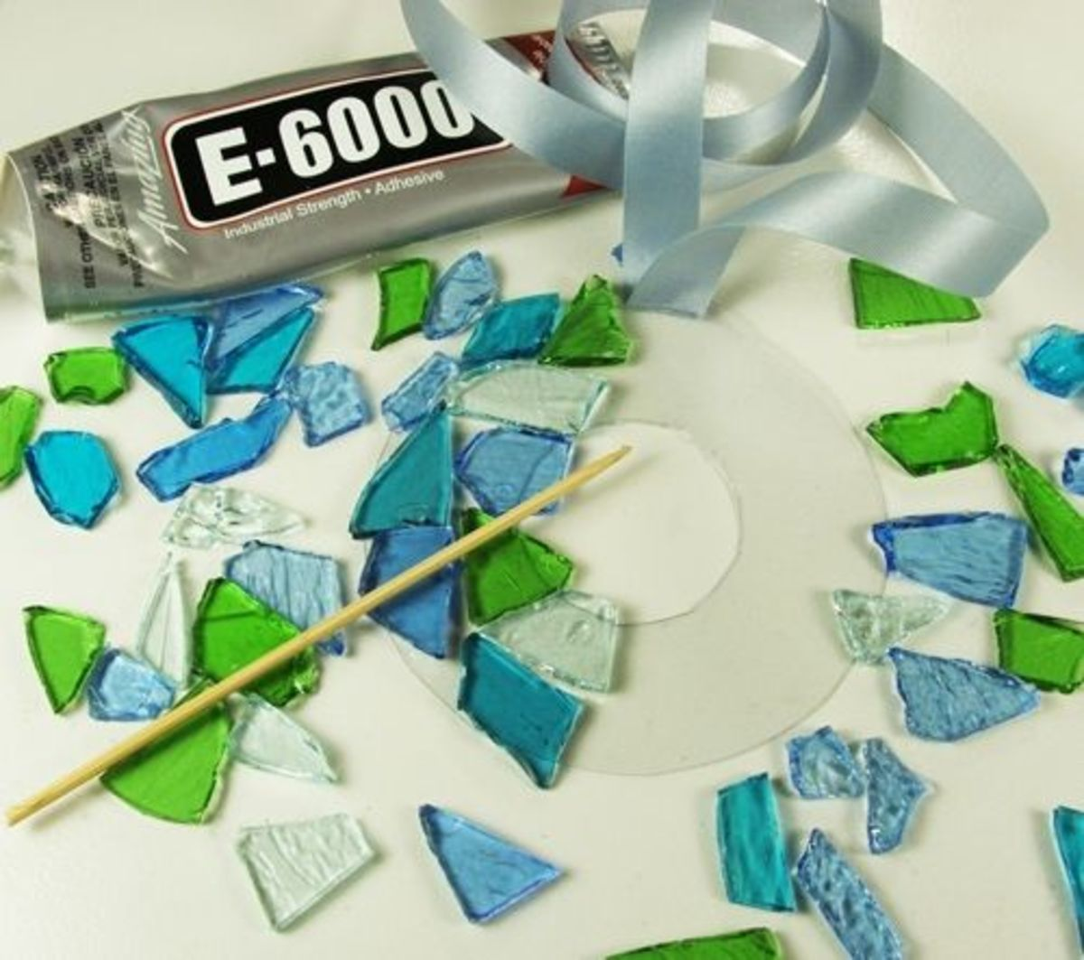 6. To adhere the cobbles take a small drop of glue onto a wood skewer or toothpick then smear the adhesive onto a cobble then place the piece of glass on to the plastic circle starting with the outside edge. It is perfectly okay to have the cobbles e
