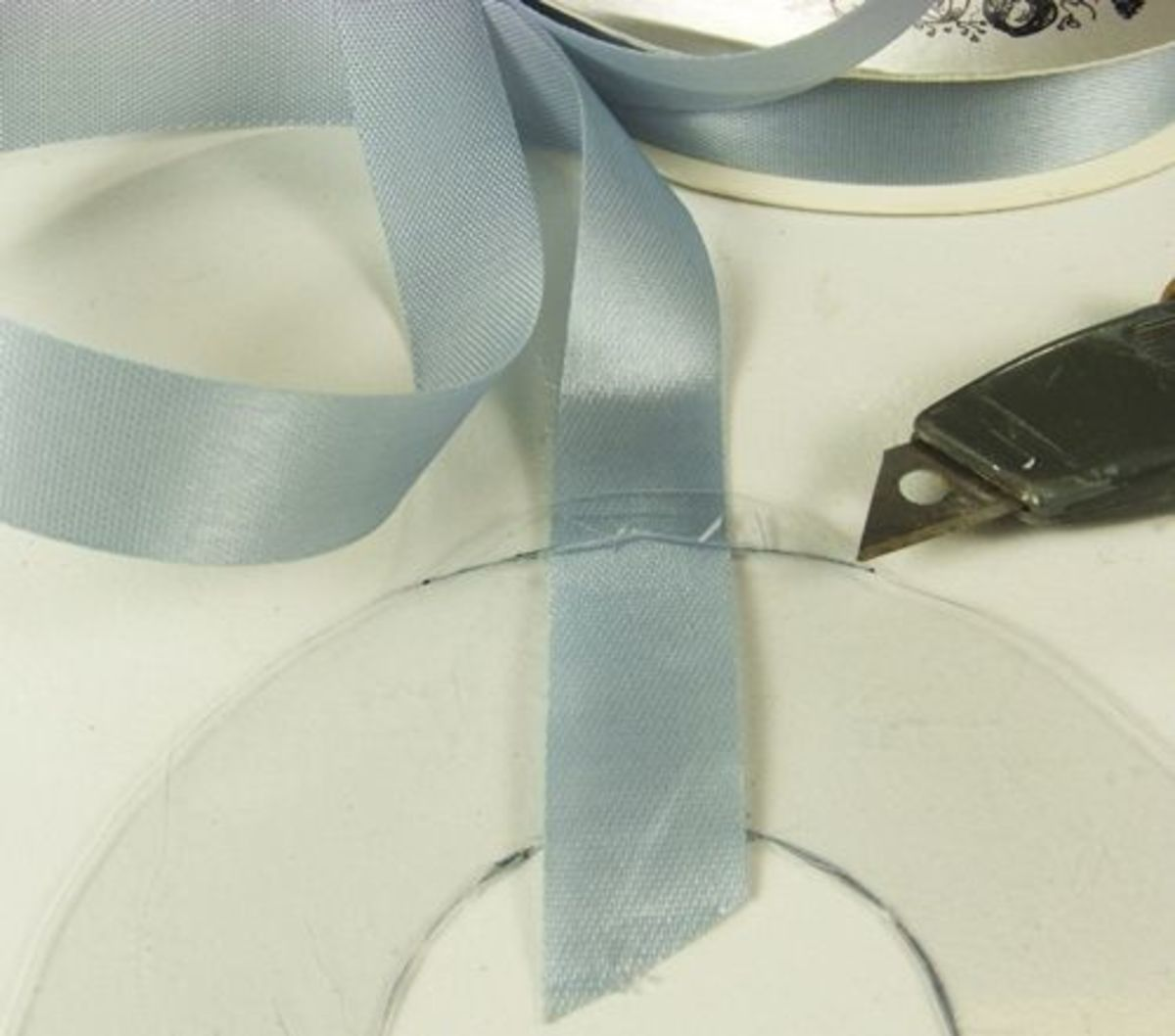 3. Cut a small slit the width of your ribbon along the base of the hanging tab following the curve of the circle. Insert the ribbon pulling it through until both ends are equal in length. It is important that the ribbon be added before you glue on th