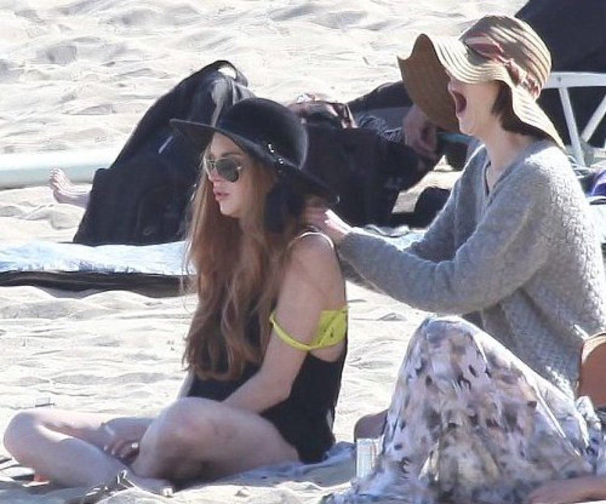 Even celebrities do it: Ali Lohan massages Lindsay Lohan's shoulders as they relax on the beach in Los Angeles.