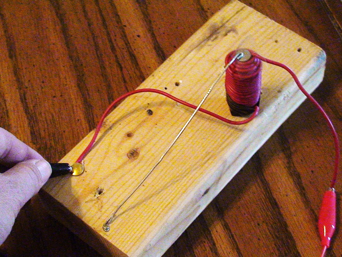 Use the alligator clip attached to the negative end of the battery to tap the thumb tack and listen to Morse code.