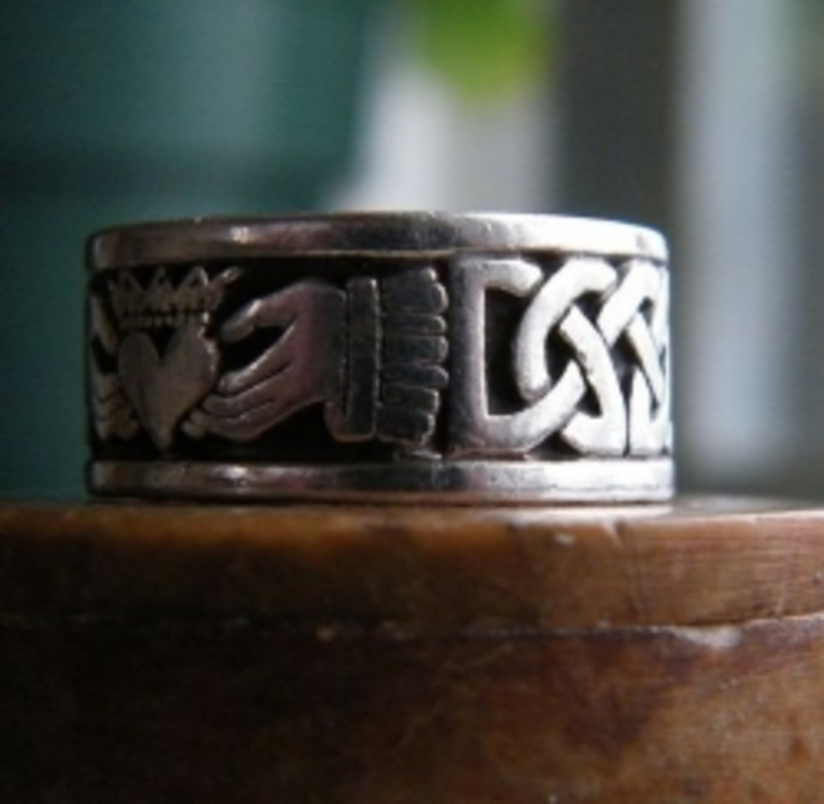 Bold design with Claddagh central icon connected by never ending braid in a finely worked ring.