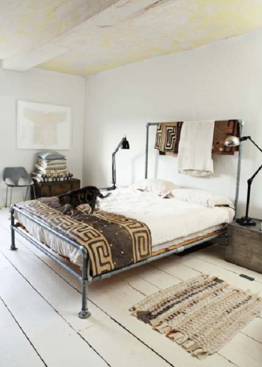 A modern tribal bedroom layout with a rustic floor finish, modern chair, and contemporary table/reading lamps.