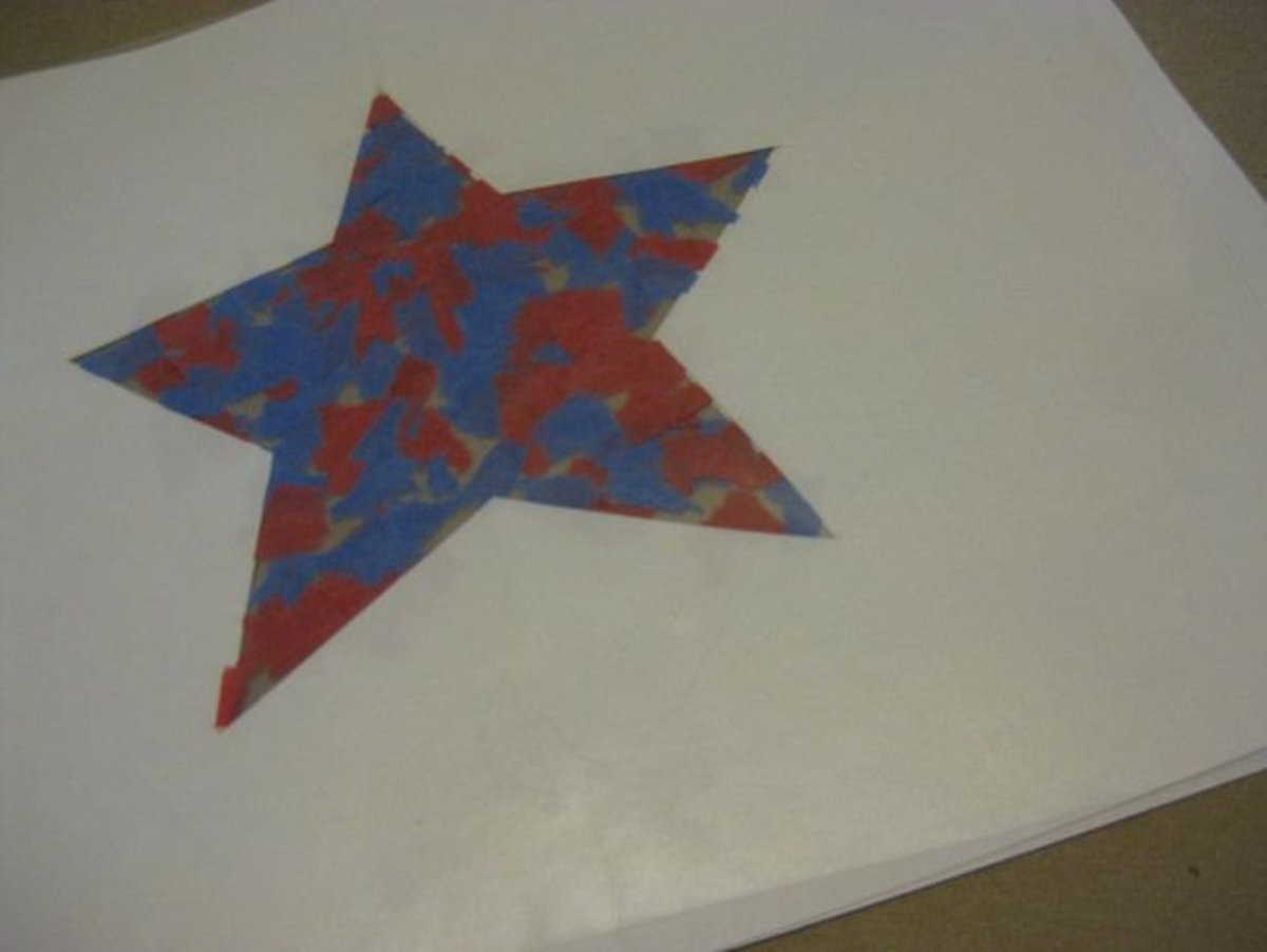 With the second paper star placed on top of the tissue paper, and another piece of clear contact paper on top of that.