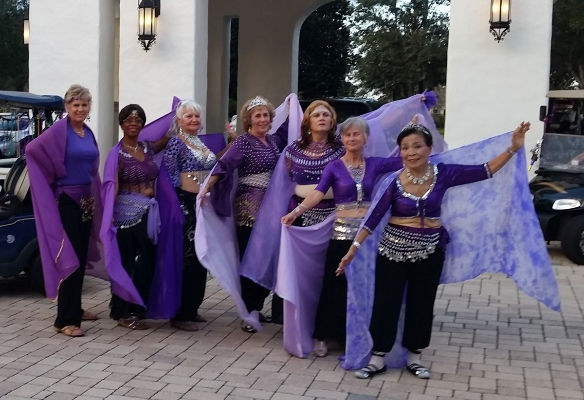 A troupe of belly dancers wearing their purple outfits.