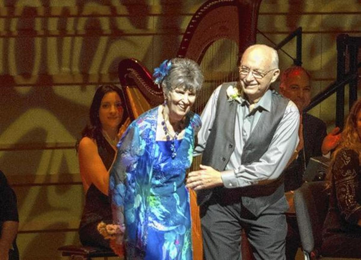 "Nancy Dufault, 72, who has Parkinson's, takes a bow after dancing the tango with her husband, Bob, at ""Symphonic Suite for Healing."""