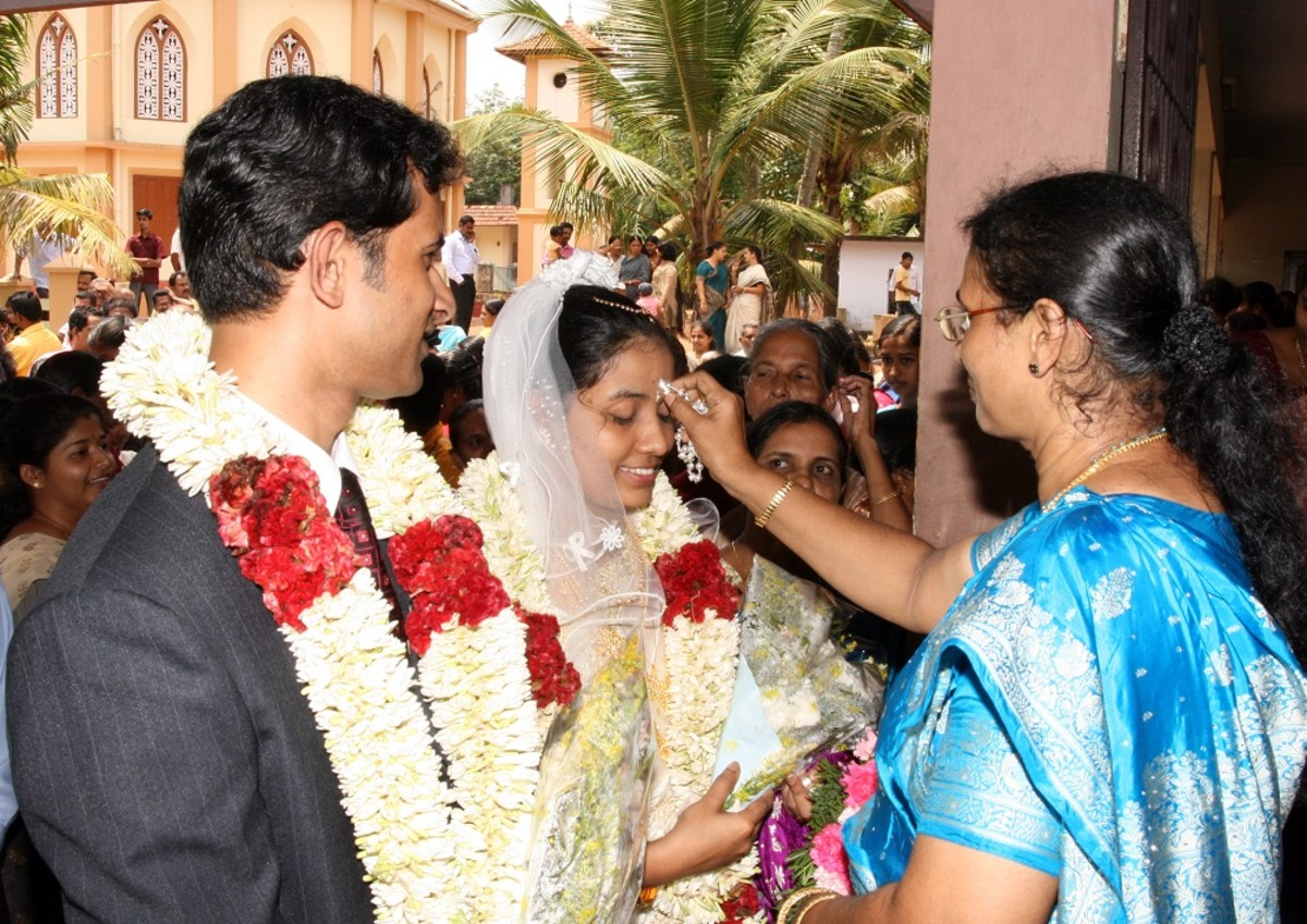 Mother of groom, blessing both bride and groom