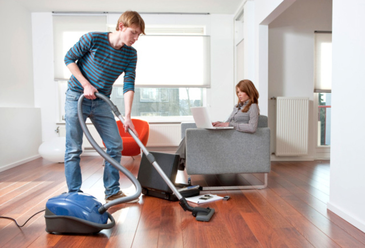 Man cleaning the house while spouse sits surfing the net