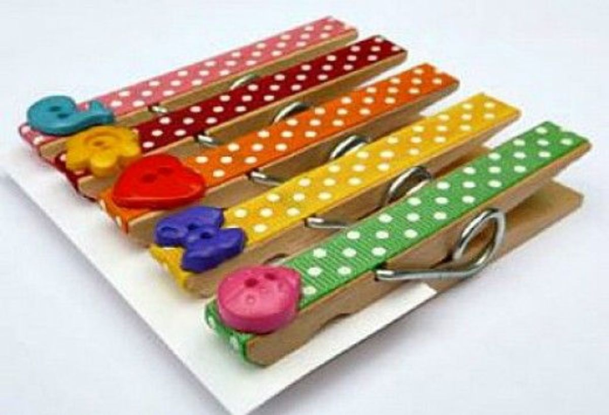 Cover a clothes pin with ribbon and buttons. Use them on a desk or add a magnet to use on a refrigerator