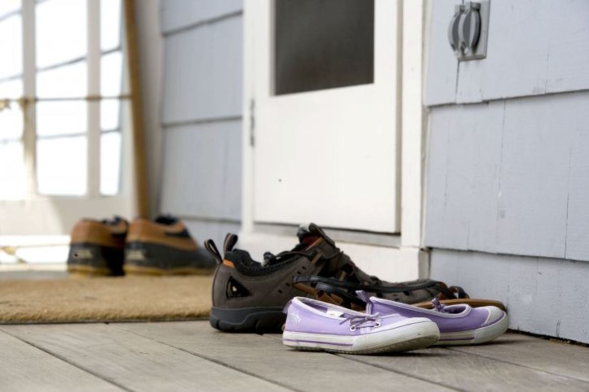 The best practice you can institute is to ask everyone to remove their shoes before entering the house to reduce the risk of bringing contaminants into the home.  Clean shoes with a sanitizing shoe mat, sanitizer wipes or a sanitizer sprayed on the