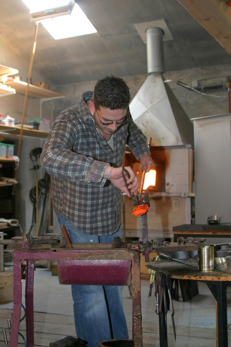 An artist working at his craft of blowing glass into selected objects of beauty.