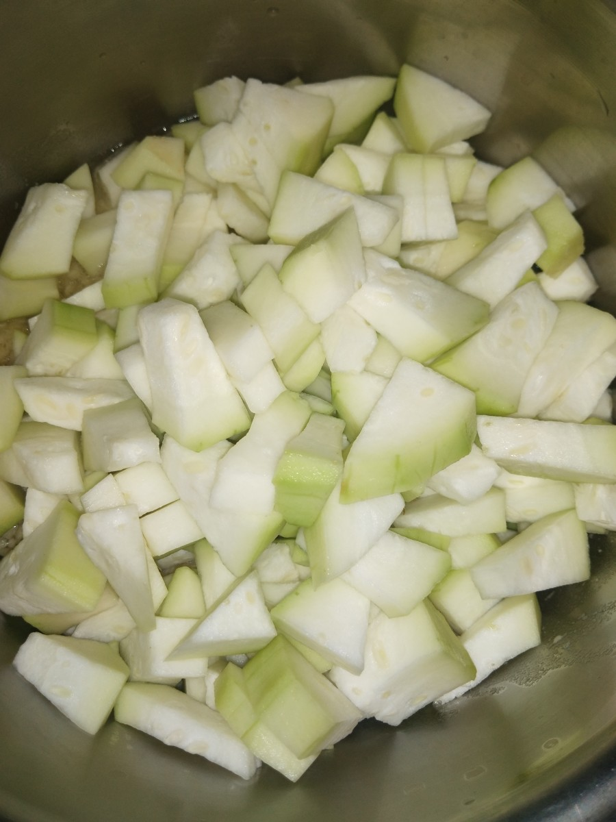 Transfer cooked dal and cubed bottle gourd to vessel, pan or pot.