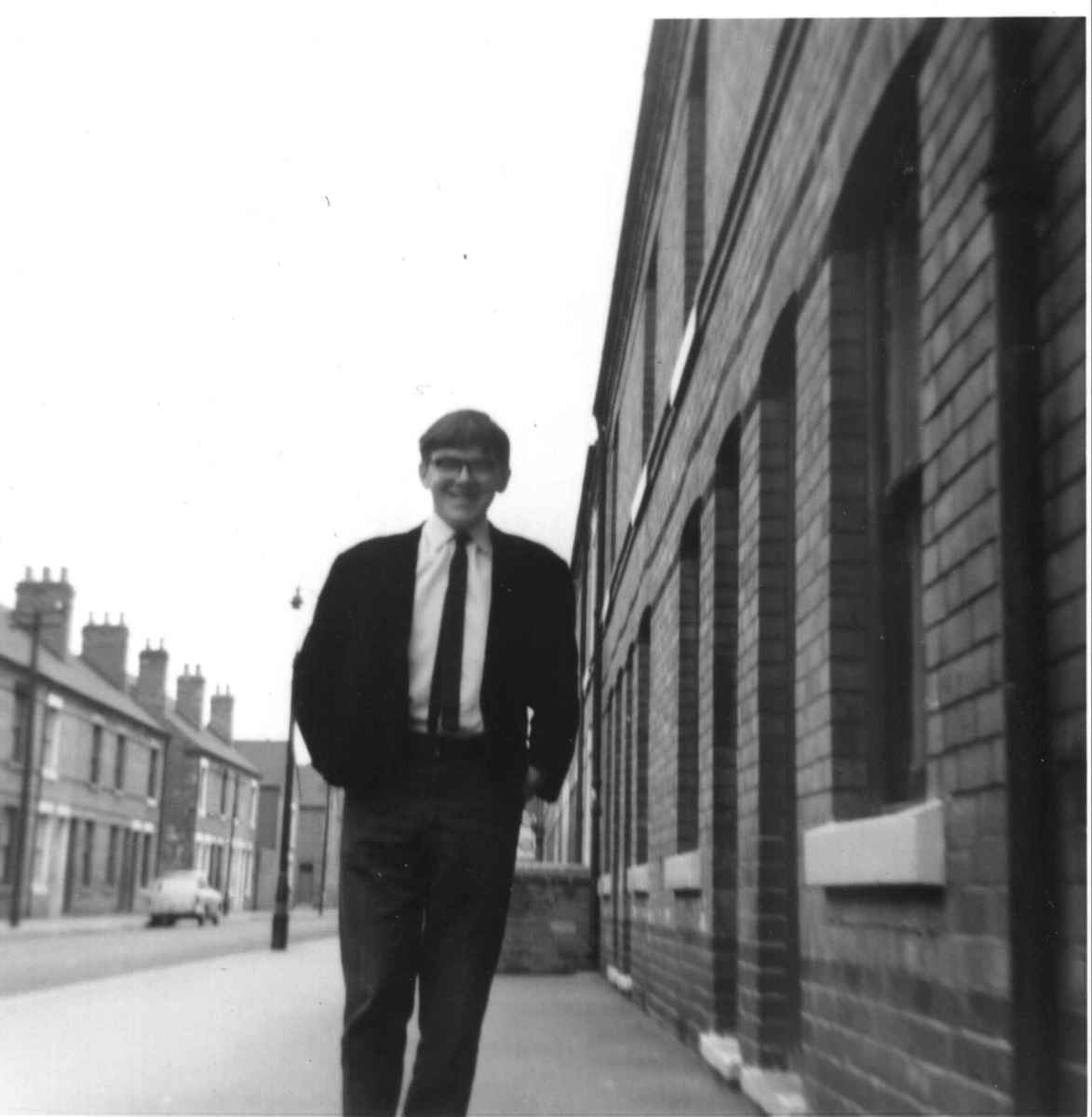 My brother standing on the street outside the house where I grew up