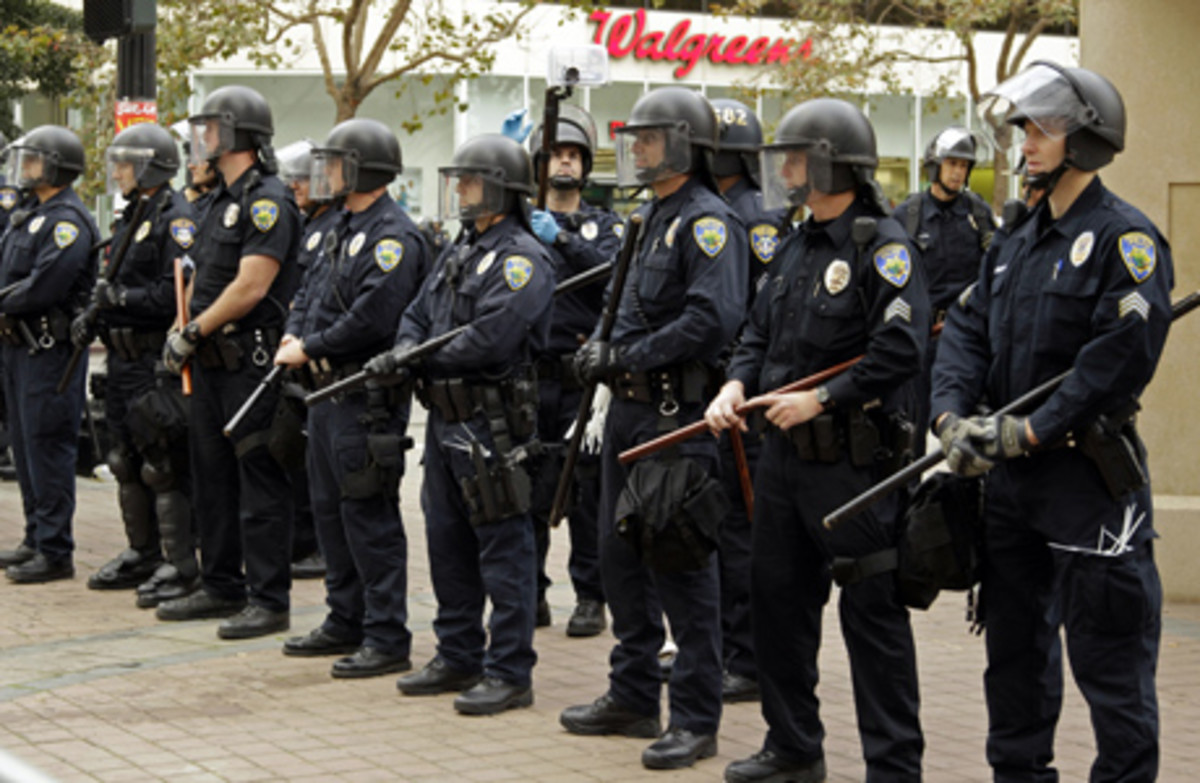 Oakland police officers in riot gear line Frank H. Ogawa plaza, the site of an Occupy Wall Street encampment,