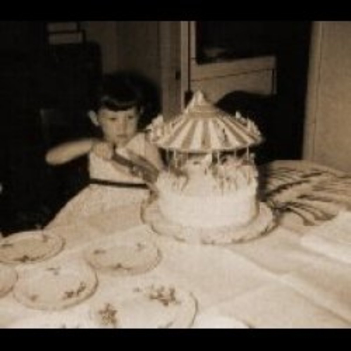 That's me, at the age of four or five. My mom took the picture, or my dad... not sure which one, really. Mom used to buy lovely birthday cakes from the bakery. This one was a carousel with animal figurines on it.