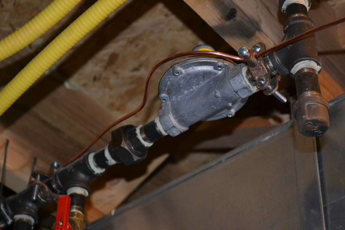 My gas line is now grounded: copper wire attached to the black iron pipe on either side of the aluminum regulator