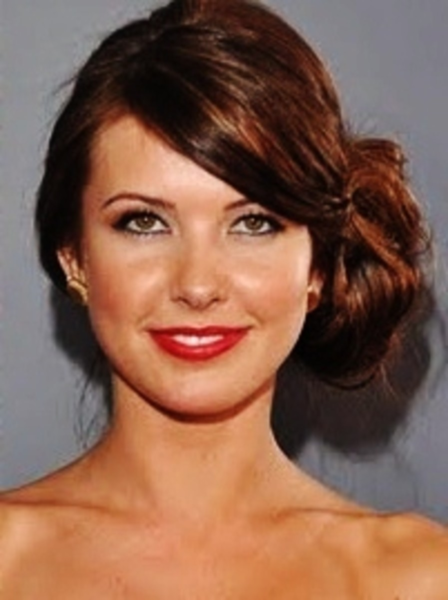 Audrina Patridge wears cocoa colored hair in a bun on the side of her head.