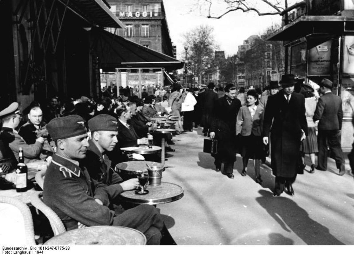 "German soldiers and officers mingling with French population on a sunny but still cold day of 1941. The cafe in this picture is most likely to be ""Les Deux Magots"" on Boulevard Saint- Germain"