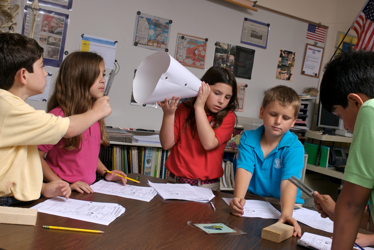 This group of students is employing several different learning methods at the same time: one student is writing, another is participating, another is watching, and another is listening to the results of the experiment.