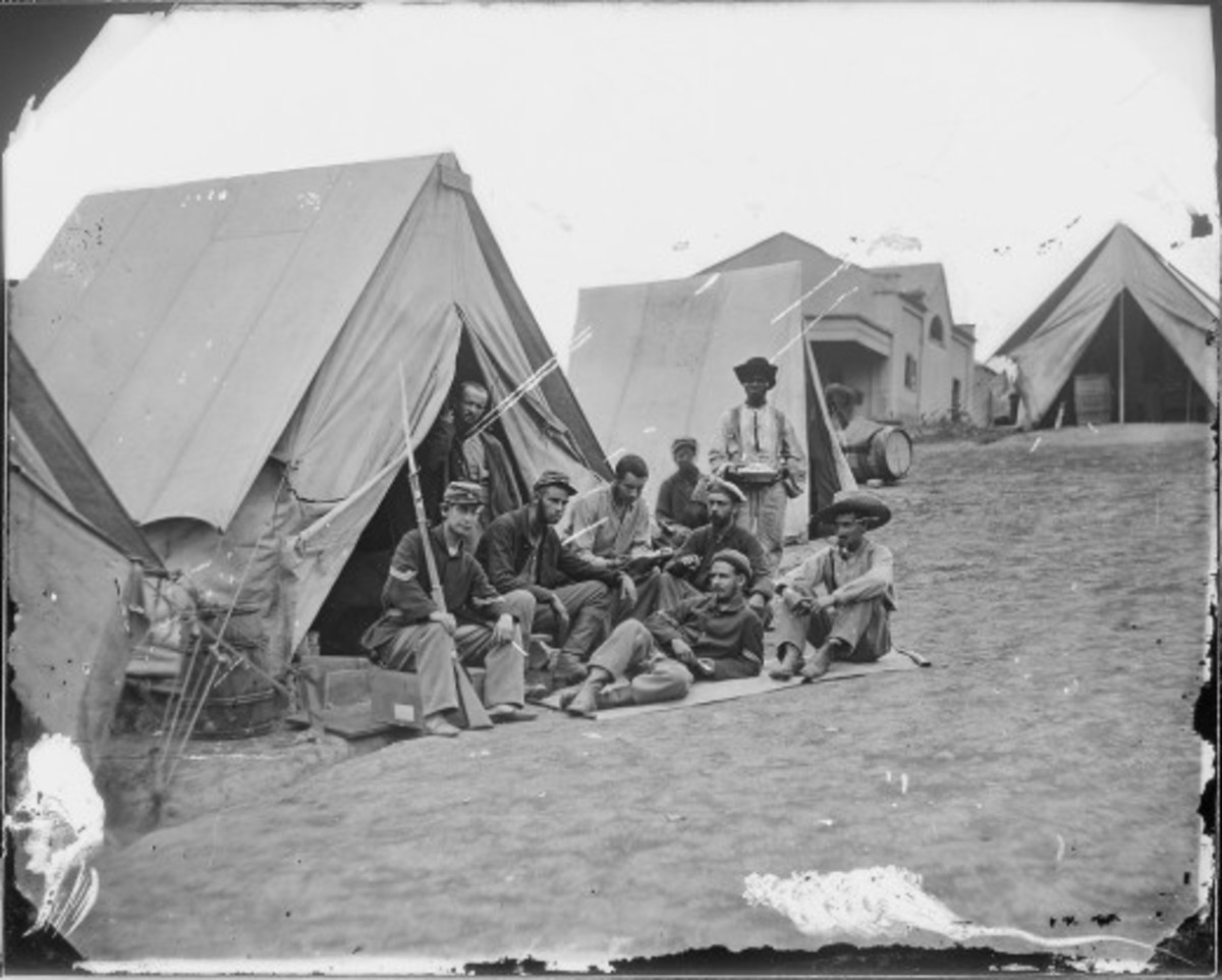 A camp servant poses for a photograph with troops in his Company
