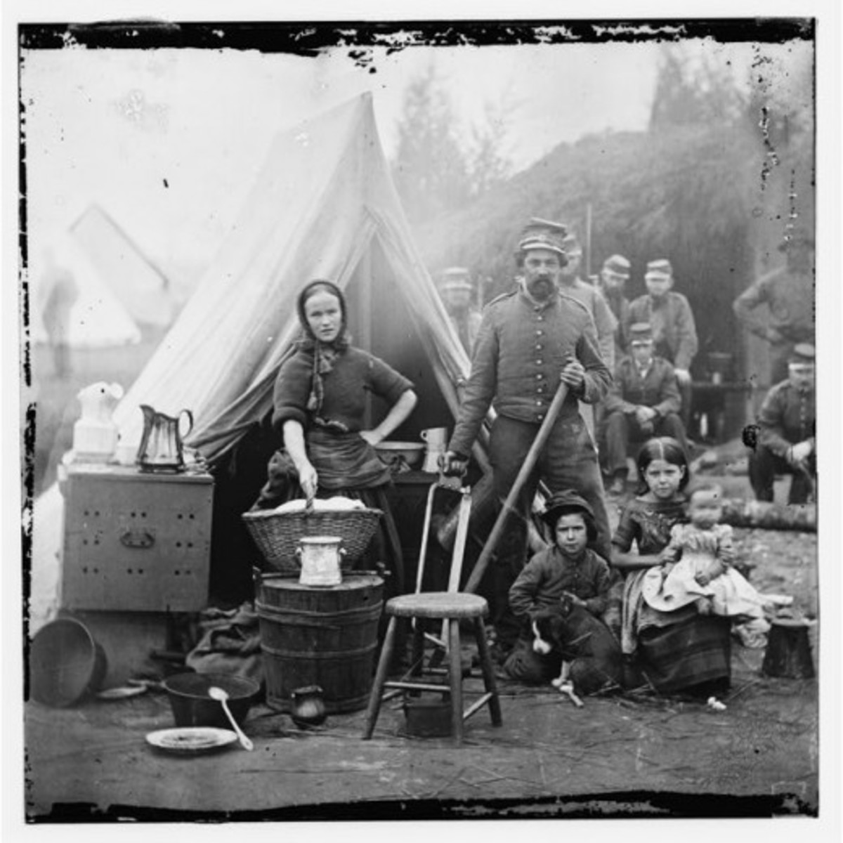 A wife and three children join a soldier in his camp. The wife holds a basket of laundry, so this was no holiday outing for her