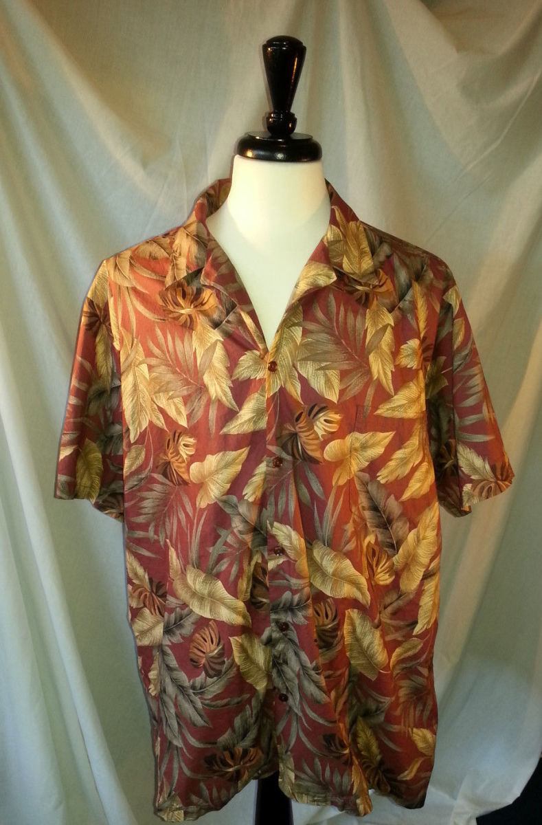 This Hilo Hattie shirt features a casual yet fun sophisticated Hawaiian print with a brick red background with a variety of gold and green leaves.