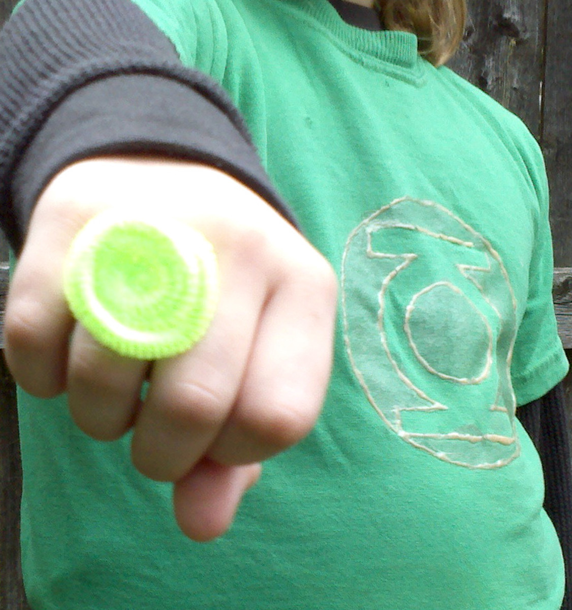 A child transforms into a Green Lantern with a green t-shirt with painted logo and a ring made from a pipe cleaner.